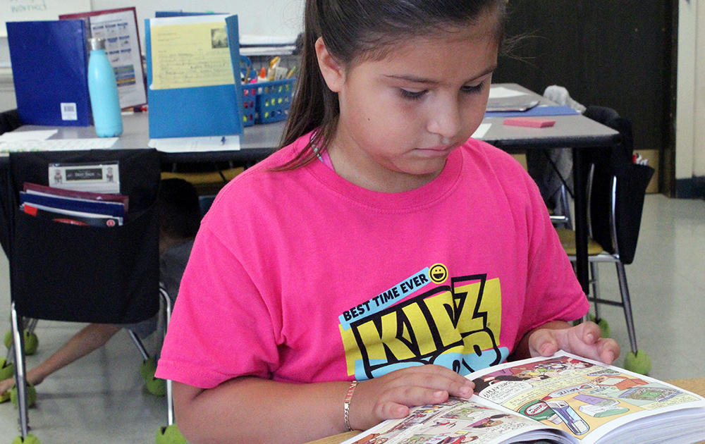 A female student sits at a work table reading a book in Ms. Traci Dean's 3rd-grade classroom.