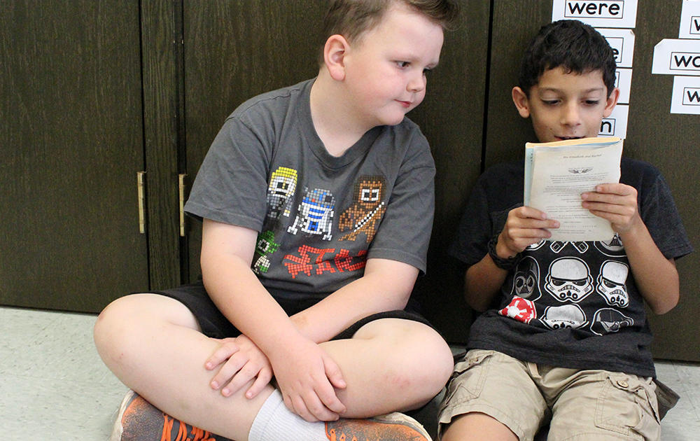 Two male students sit on the floor sharing a book in Ms. Traci Dean's 3rd-grade classroom.