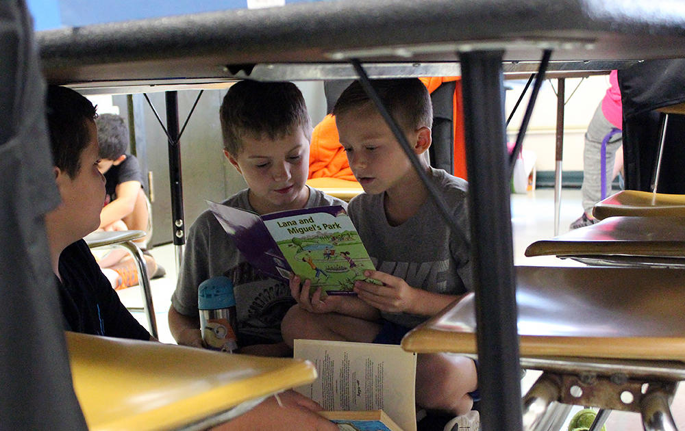 Three male students sit under a work table sharing a book in Ms. Traci Dean's 3rd-grade classroom.