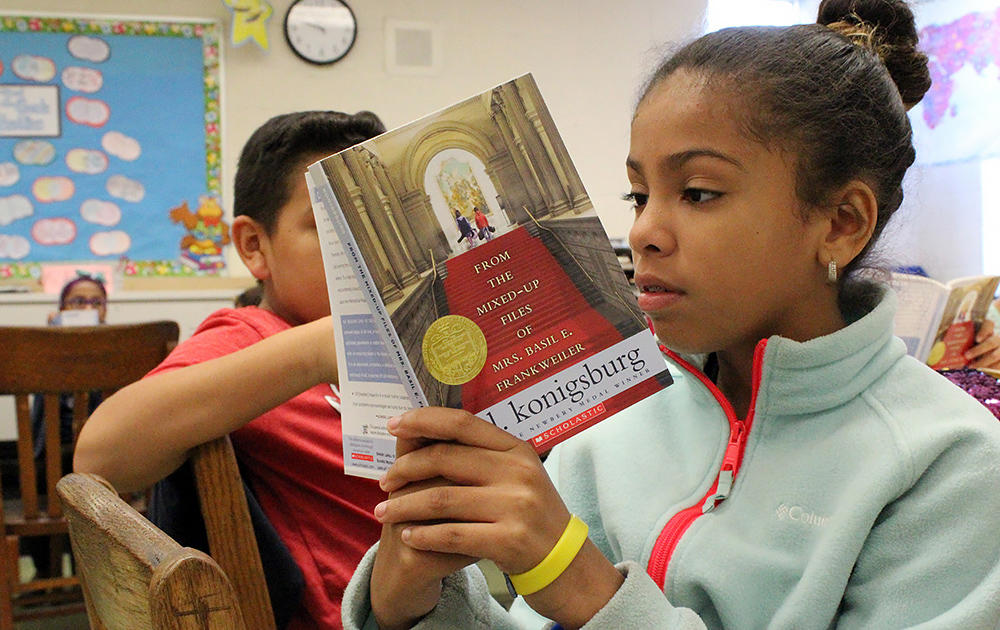 A female student in the right foreground reads a novel in Ms. Elizabeth Murray's 5th-grade class. A male student in the left background also reads.