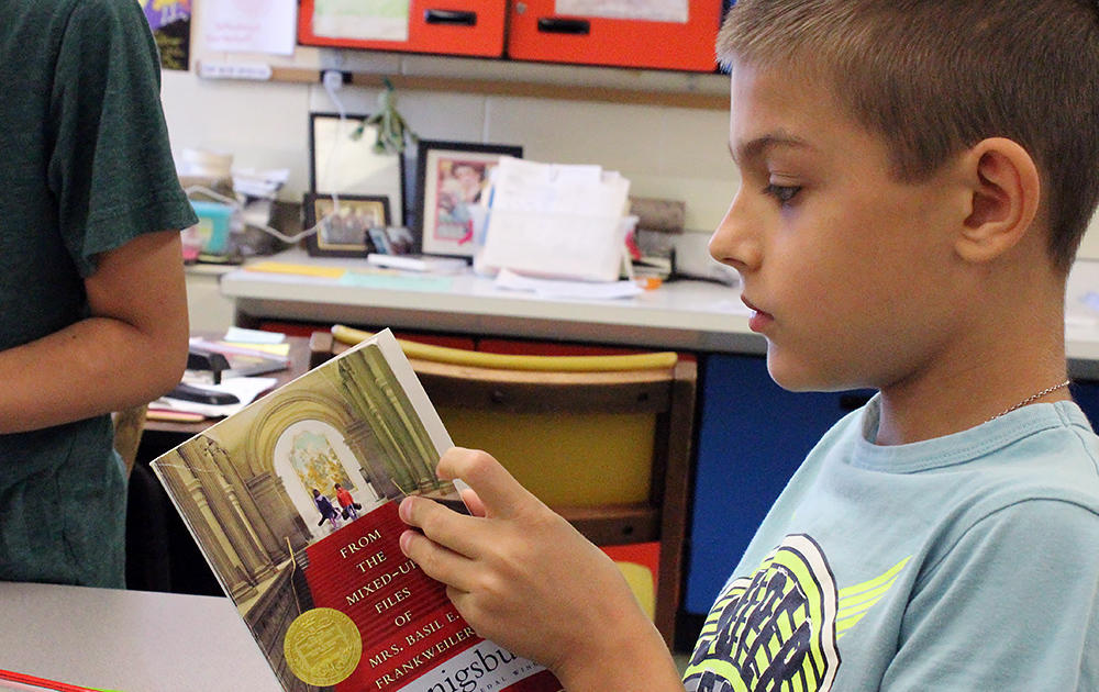 A male student reads a novel in Ms. Elizabeth Murray's 5th-grade class.