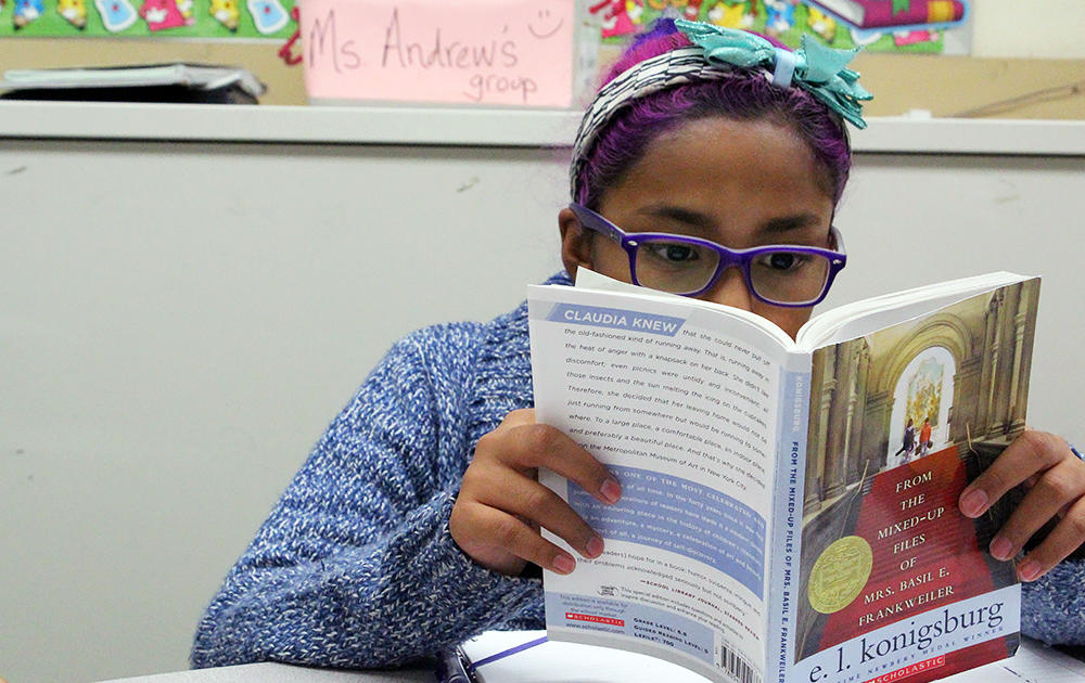 A female student reads a novel in Ms. Elizabeth Murray's 5th-grade class.