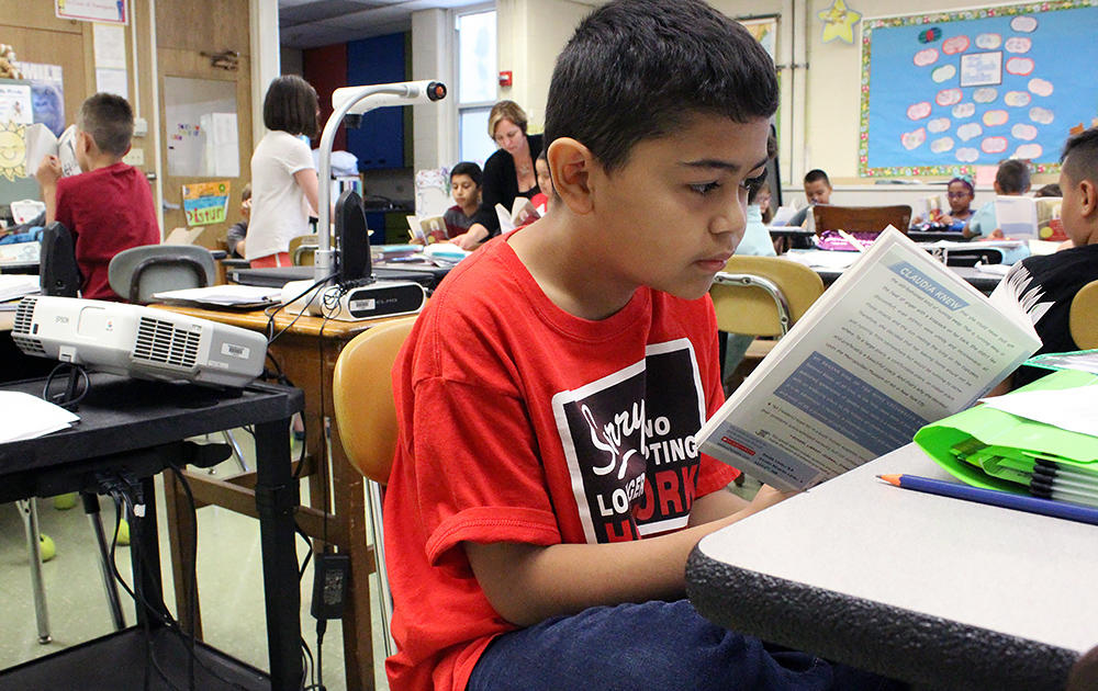 A male student reads a novel in Ms. Elizabeth Murray's 5th-grade class. Other students in the background also read.