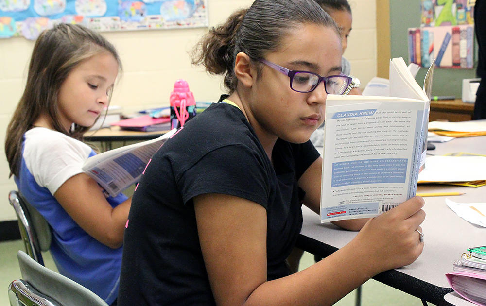 Three female students sit at a work table and read a novel in Ms. Elizabeth Murray's 5th-grade class.