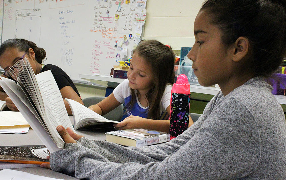 Three female students read a novel in Ms. Elizabeth Murray's 5th-grade class.