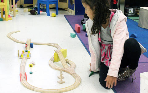 A female student inspects a toy train set while attending the Early Childhood Center's Fall 2017 Open House.