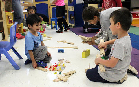 Male students play on a classroom floor while attending the Early Childhood Center's Fall 2017 Open House.