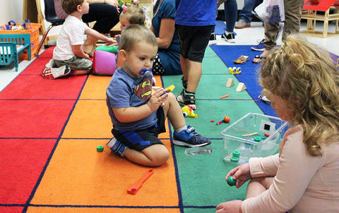 Students play on a classroom floor while attending the Early Childhood Center's Fall 2017 Open House.