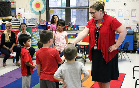 A teacher leads students in a handshaking activity during the Early Childhood Center's Fall 2017 Open House.