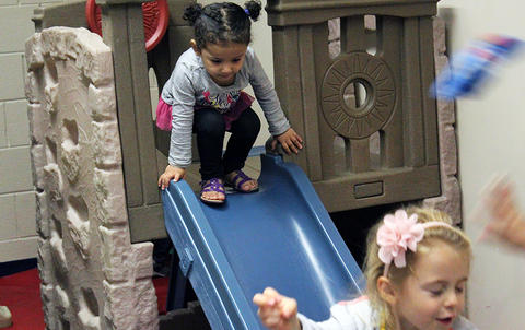 A student gets ready to go down a slide in the ECC all-purpose room during the Early Childhood Center's Fall 2017 Open House.