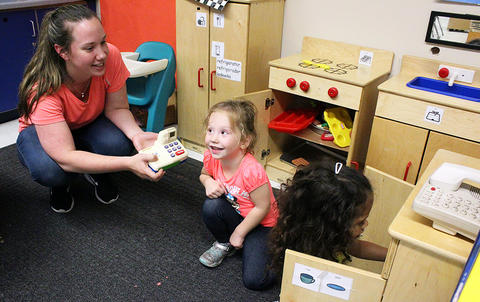 A mother and daughter play in a toy kitchen while attending the Early Childhood Center's Fall 2017 Open House.