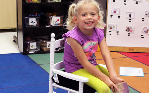 A female student sits in a wooden chair while attending the Early Childhood Center's Fall 2017 Open House.