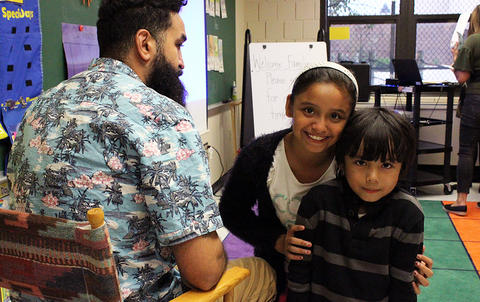 Two students look at the camera while their father is seated nearby during the Early Childhood Center's Fall 2017 Open House.