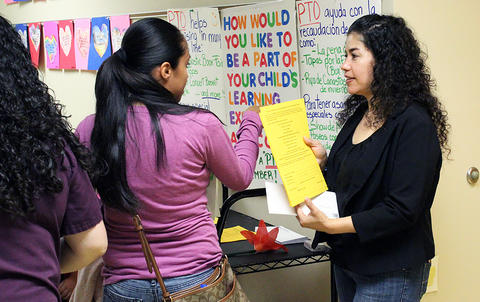 A parent and a member of the PTO talk in the hallway during the Early Childhood Center's Fall 2017 Open House.