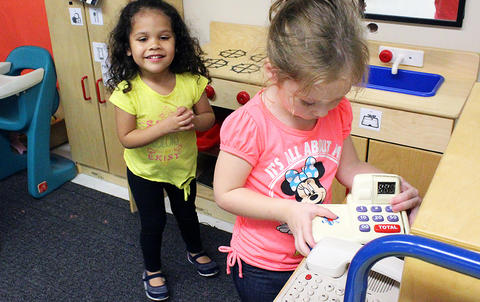 Two female students play in a toy kitchen while attending the Early Childhood Center's Fall 2017 Open House.
