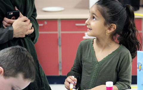 A student looks up at her mother while attending the Early Childhood Center's Fall 2017 Open House.