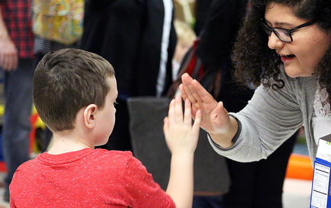 A student high fives a teacher during the Early Childhood Center's Fall 2017 Open House.