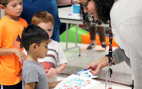 A student shows his drawing to a teacher during the Early Childhood Center's Fall 2017 Open House.