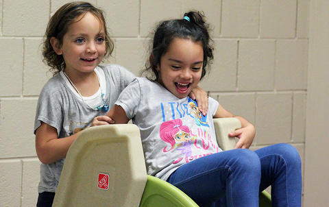 Two female students play on a slide in the all-purpose room during the Early Childhood Center's Fall 2017 Open House.
