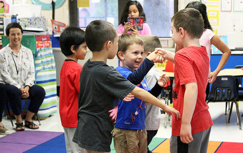 Students participate in a handshaking activity during the Early Childhood Center's Fall 2017 Open House.