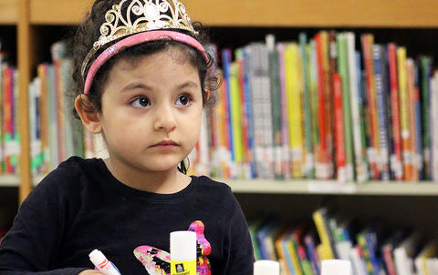 A student wears a paper crown while working an art activity during the Early Childhood Center's Fall 2017 Open House.