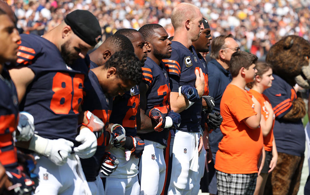 Nathan Calderon stands on sideline with the Chicago Bears during the playing of the National Anthem.