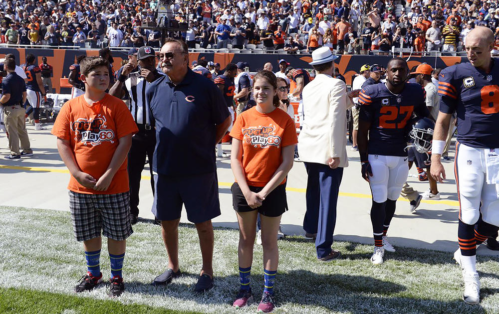 Elm 8th-grader Nathan Calderon (left) stands on the Bears sideline with Hall of Famer Dick Butkus. Nathan's fellow FUTP 60 state ambassador, Grace from Mount Prospect, is on the right.
