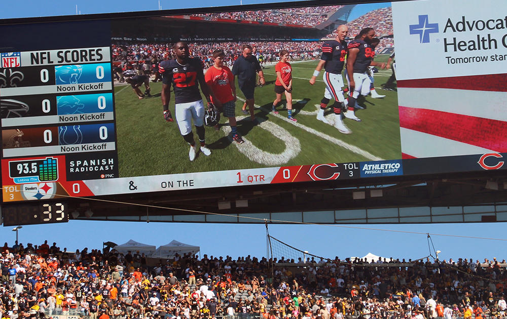 Soldier Field's videoboard shows Elm 8th-grader Nathan Calderon as he approaches midfield with Dick Butkus and fellow FUTP 60 state ambassador Grace for the pregame coin toss.