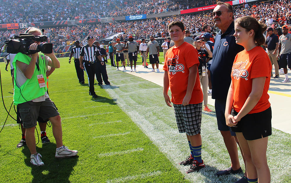 Elm 8th-grader Nathan Calderon is filmed on the Bears sideline along with Dick Butkus and fellow Fuel Up to Play 60 state ambassador Grace.