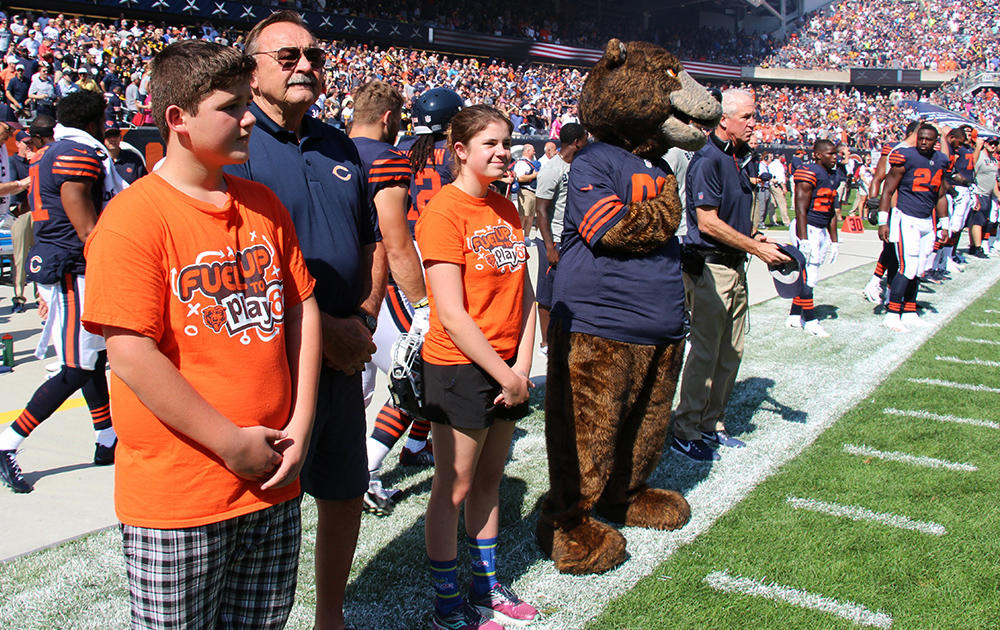 Elm 8th-grader Nathan Calderon stands on the Bears sideline with NFL Hall of Fame legend Dick Butkus and fellow Fuel Up to Play 60 state ambassador Grace.