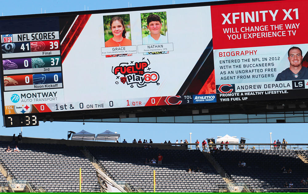Nathan Calderon and his fellow Fuel Up to Play 60 student ambassador Grace are shown on the Soldier Field videoboard along with the FUTP 60 logo.