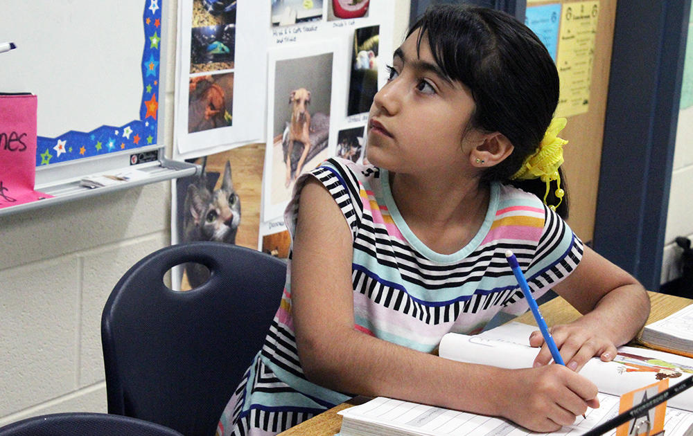 An Elmwood 2nd grader turns her head and looks at the white board during a reading lesson.
