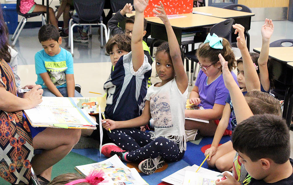 Elmwood 2nd graders raise their hands during class while doing a reading exercise.