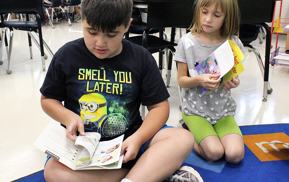 Two Elmwood 2nd graders read while sitting on the classroom floor.