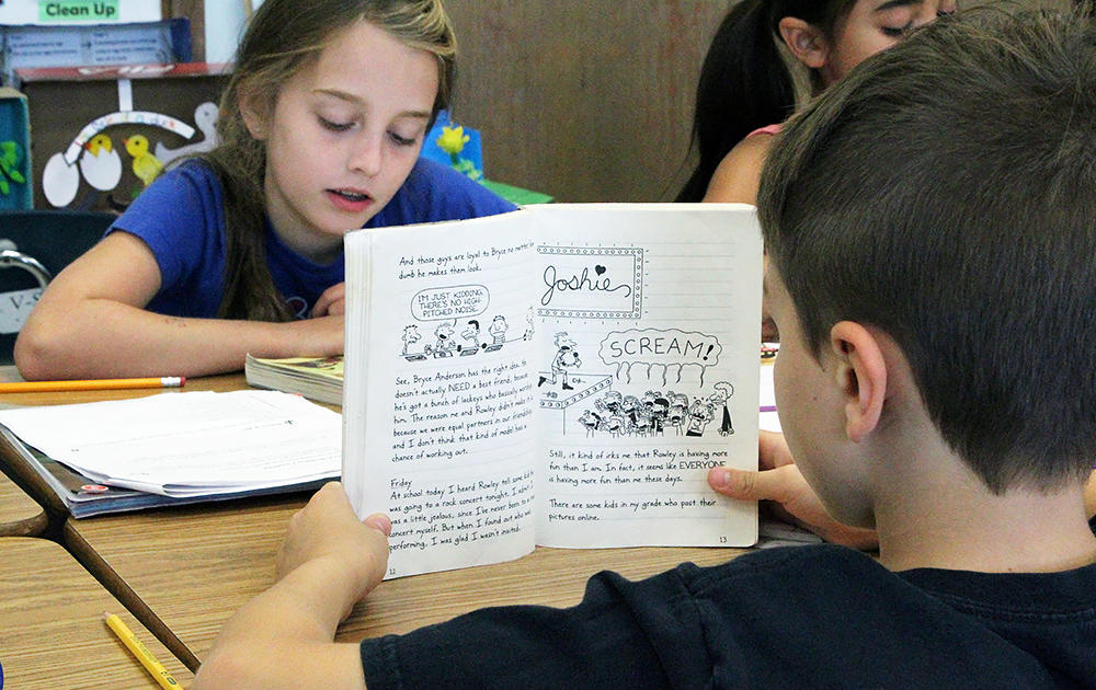 Two Elmwood 3rd graders read silently during class.