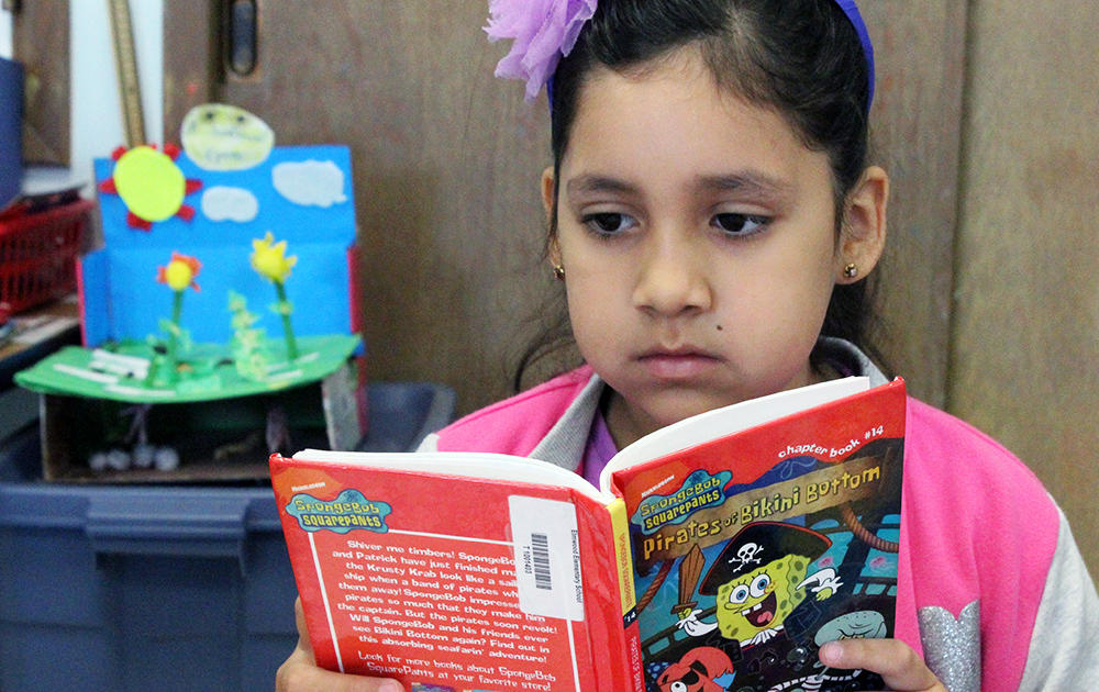 An Elmwood 3rd grader reads silently to herself during class.