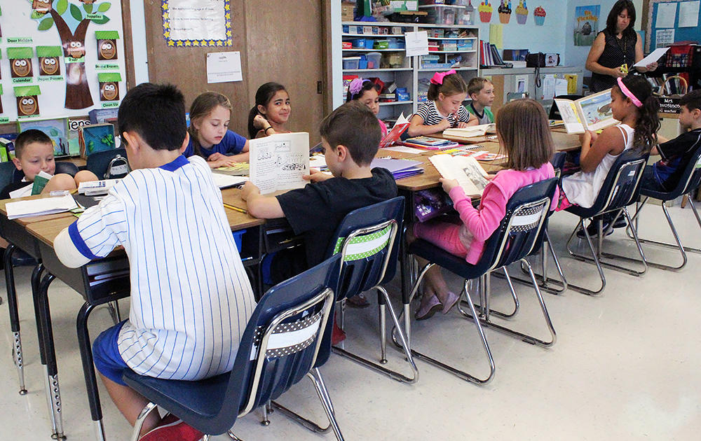 Elmwood 3rd graders sit at a communal table and read during class.