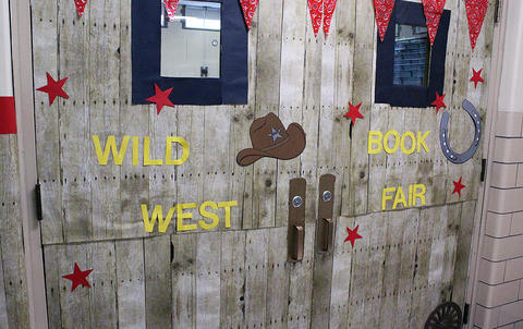 A sign on the John Mills gym doors welcomes visitors to the Wild West-themed Scholastic Book Fair.