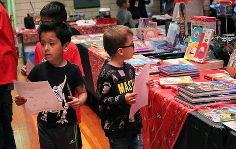 John Mills Elementary School students on a scavenger hunt browse the selections at the PTA's Fall 2017 Scholastic Book Fair.