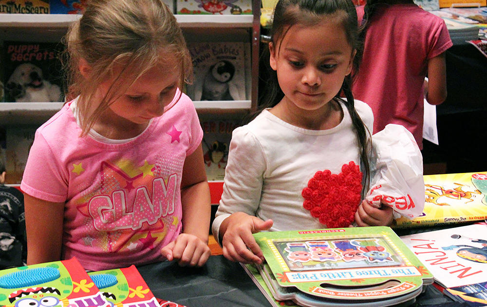 Two John Mills female students browse selections at the PTA Scholastic Book Fair.