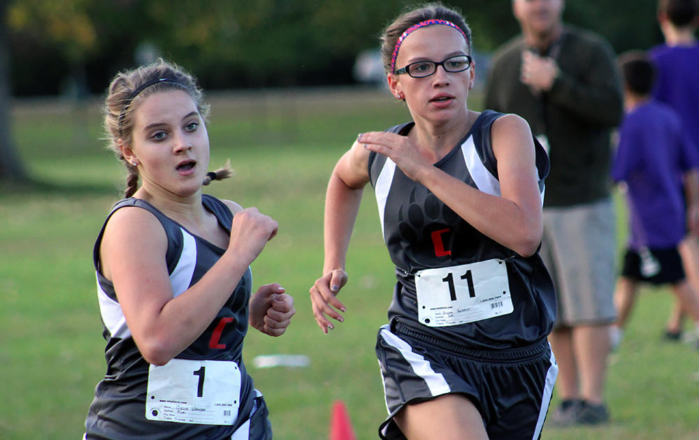 Two Elm female runners head to the finish line at the conference tournament race.