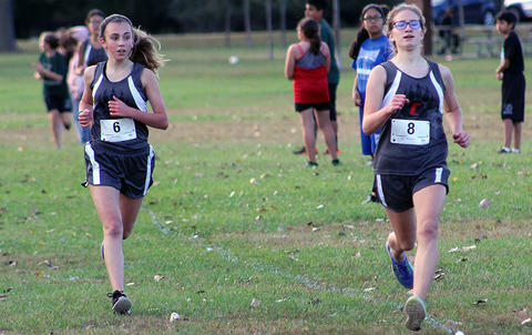Two Elm runners are neck and neck at the finish line.