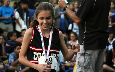 A girls runner receiving a medal for individual performance — the girls team as a whole placed second in the conference.