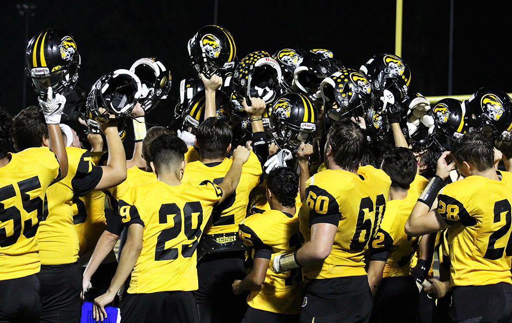 The Tigers raise their helmets to celebrate their homecoming victory over Ridgewood.
