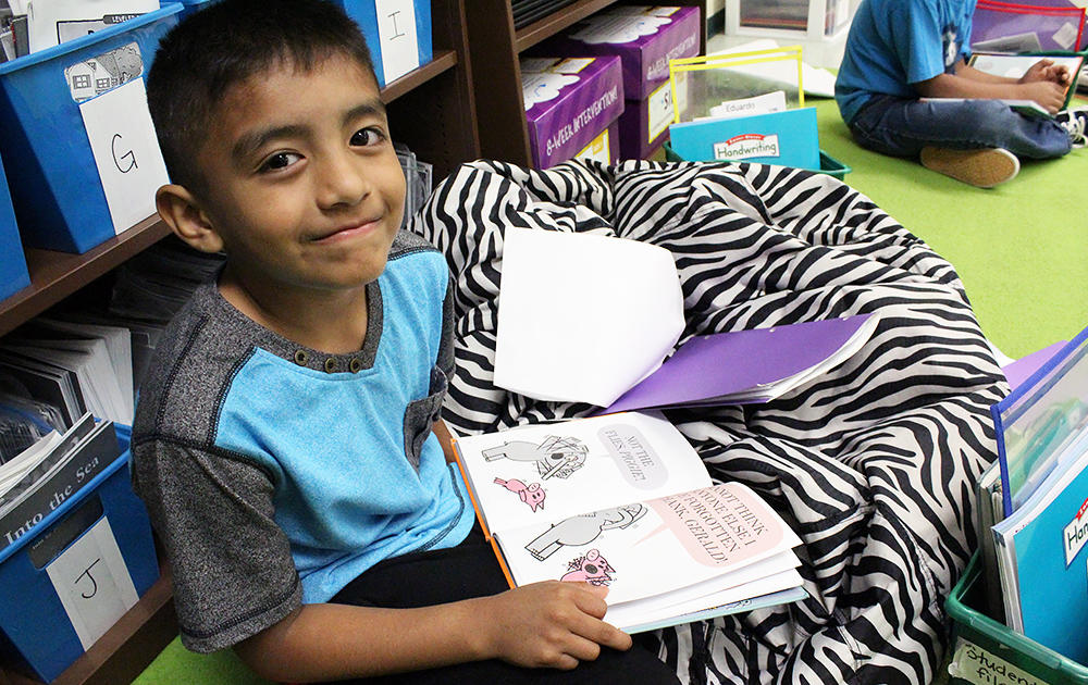A John Mills Elementary student reads a book in his English Learners class.