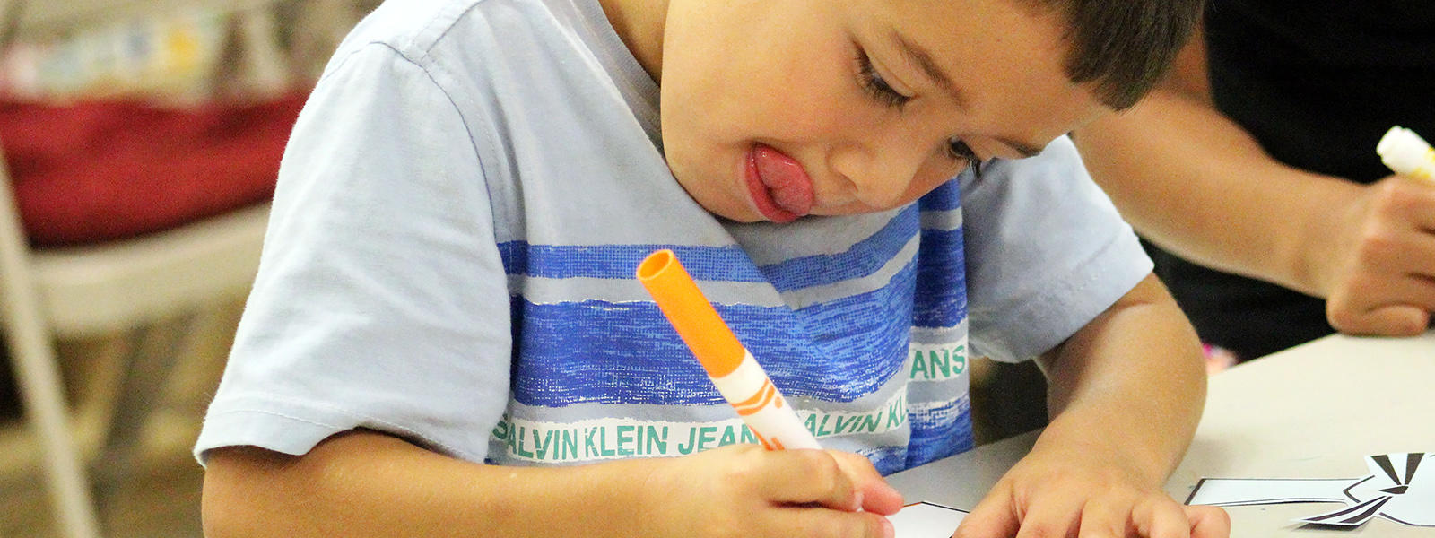 An ECC student writes at his desk as preschool screenings are announced for early March.