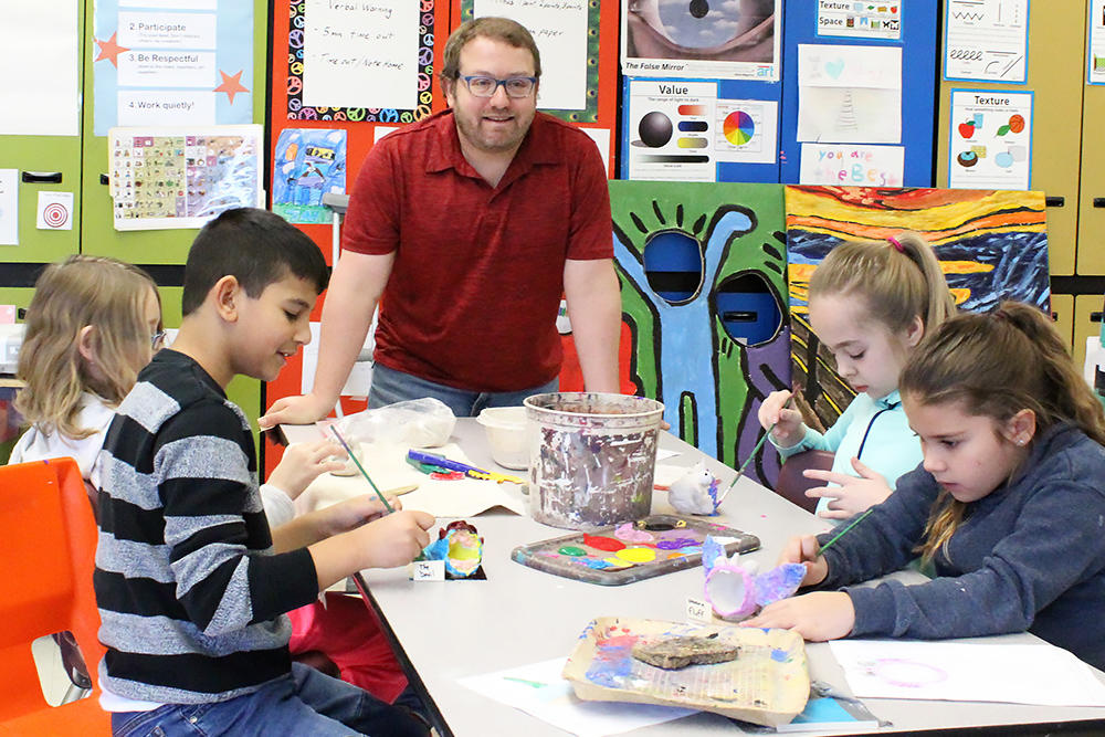 John Mills art teacher Mr. Todd Siegel monitors the progress of some of his 4th-grade students as they prepare for the school's upcoming art show.