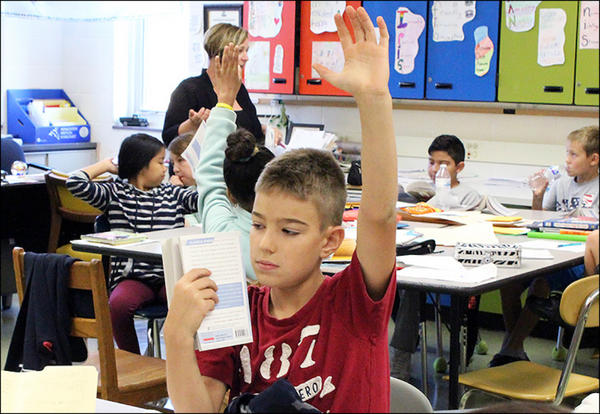 A John Mills student raises his hand in class.