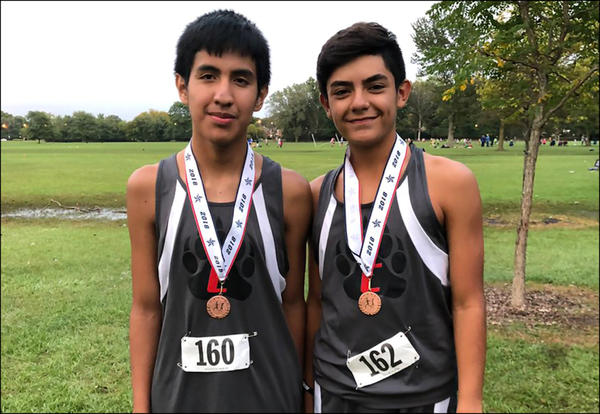 The top two Elm boys cross country finishers display their conference medals.