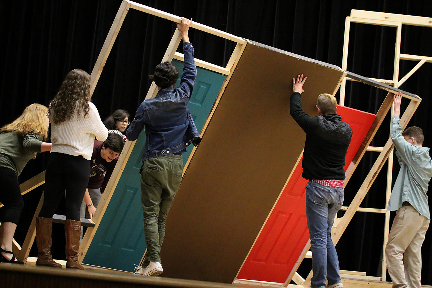 Director Noah Pligge and cast members put a wall in place during a recent rehearsal.